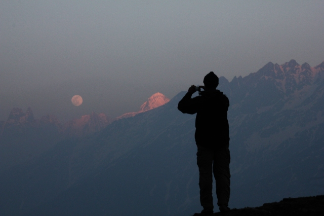 A silhouette of Vikram, a member of the team that organized this trek, against the rising moon and the Nandaghunti.